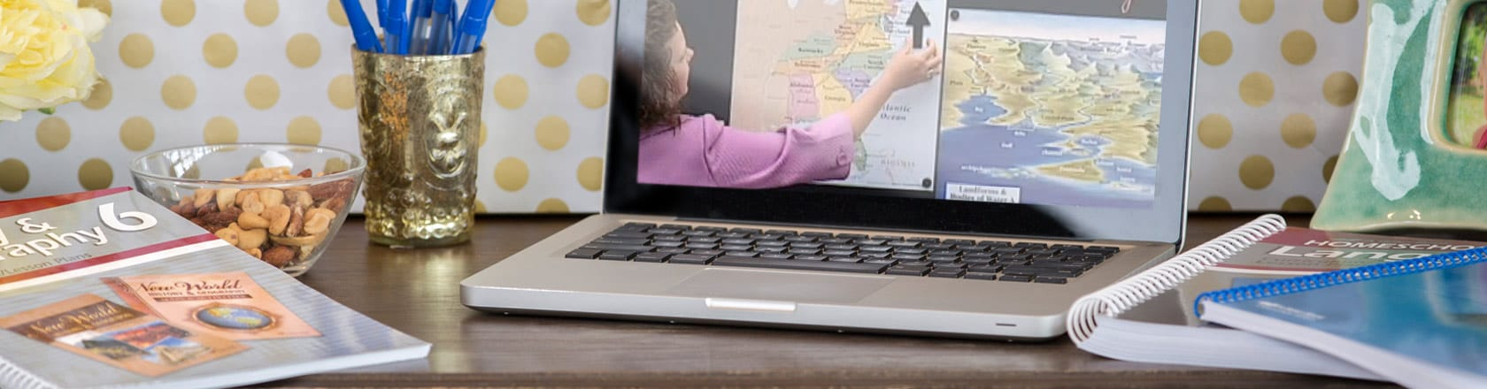 Laptop with female video teacher using map