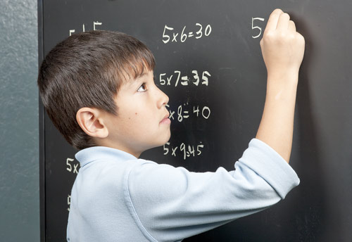 Boy multiplying on chalkboard