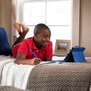Boy watching video lesson on his bed
